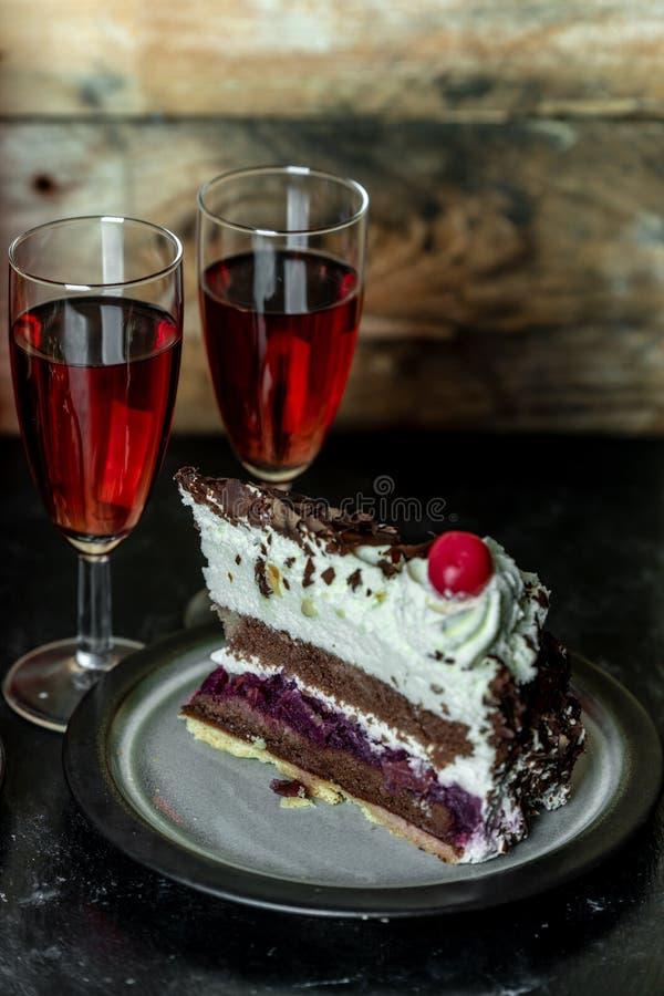 Repas doux pour deux : vin rouge et gâteau de chocolat avec la cerise et la crème fouettée image libre de droits