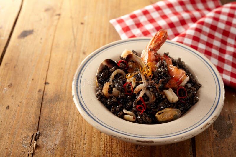 Repas gastronome de nero de risotto de mollusques et crustacés dans la cuvette près de la serviette photographie stock libre de droits