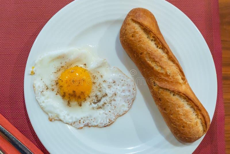 Repas simple de petit déjeuner avec l'oeuf et la miche de pain ensoleillés image libre de droits