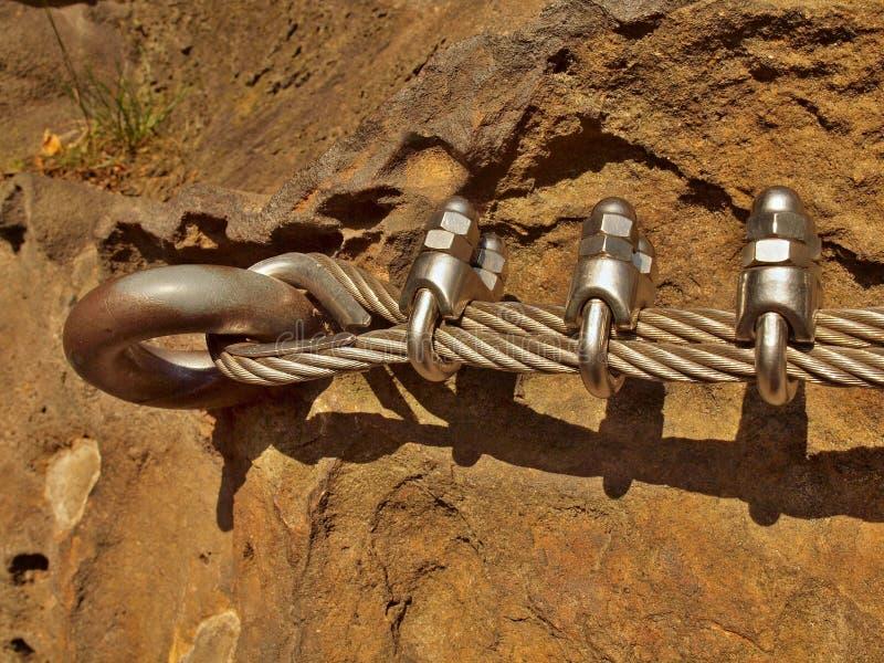 Repassez la corde tordue fixe dans le bloc par les crochets instantanés de vis Détail d'extrémité de corde ancré dans la roche photos stock
