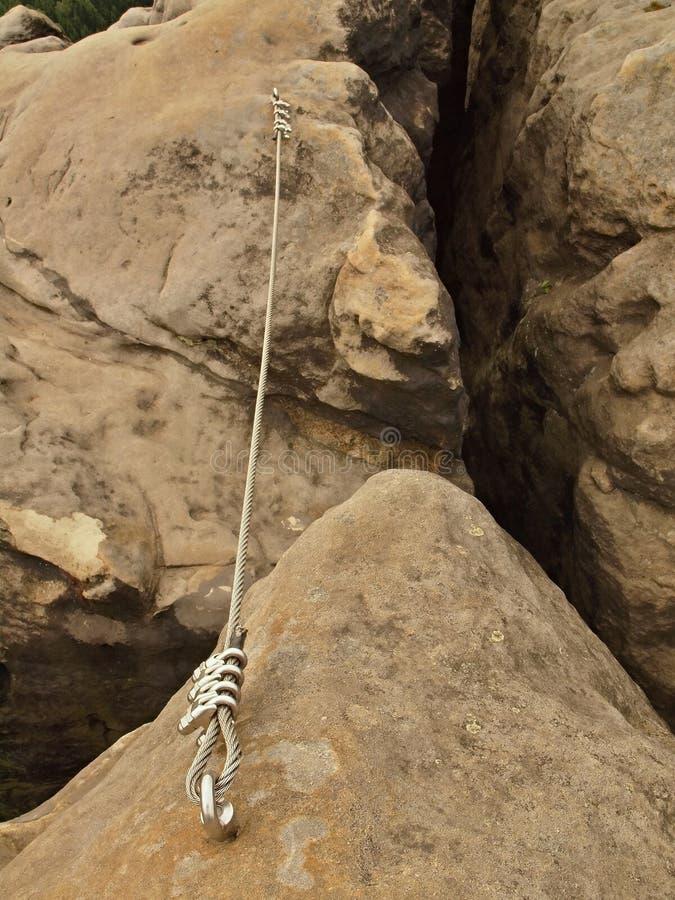 Repassez la corde tordue fixe dans le bloc par les crochets instantanés de vis Détail d'extrémité de corde ancré dans la roche photographie stock