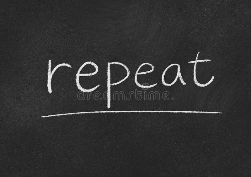 Repeat. Concept word on a blackboard background stock image