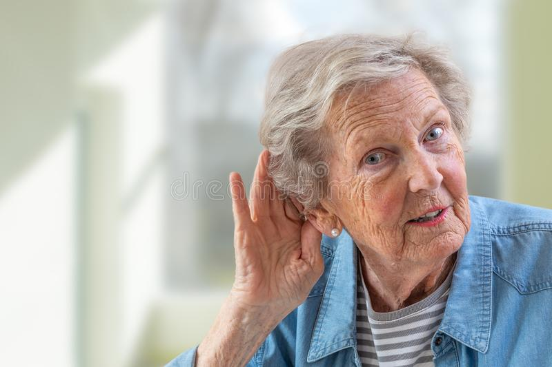 Repeat, please. Close-up of face of charming elderly woman is holding hand by her ear and struggling to hear something. Close-up of face of charming elderly royalty free stock photography