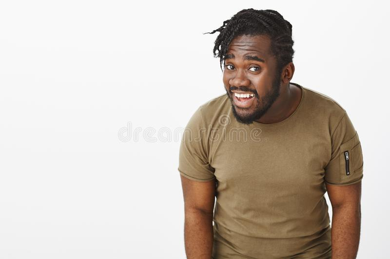 Repeat what you said. Portrait of questioned intense attractive dark-skinned guy in olive t-shirt, bending towards. Camera while asking question, standing royalty free stock photo