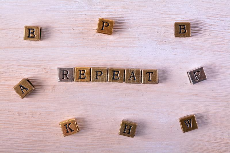 Repeat word metal block. Repeat word gold and silver metal block on white wood with letter blocks around royalty free stock image