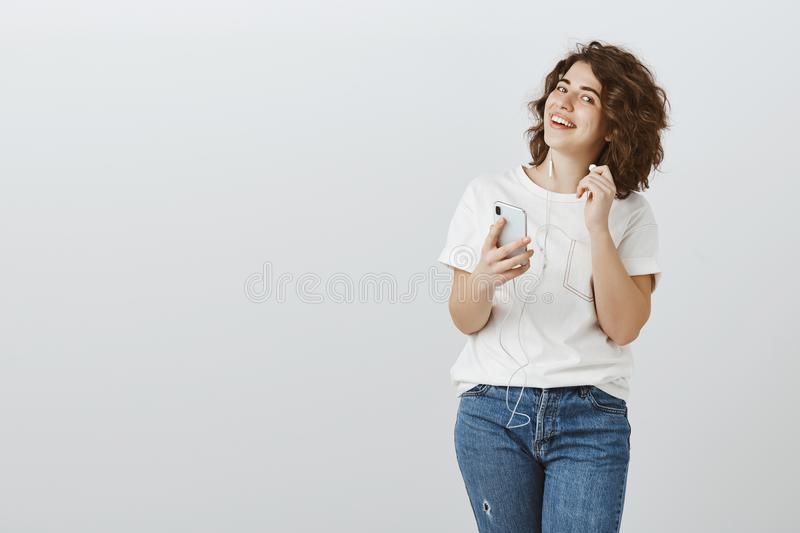 Repeat your question please. Portrait of happy bright curly-haired female studio worker, taking off earphone to hear stock photos