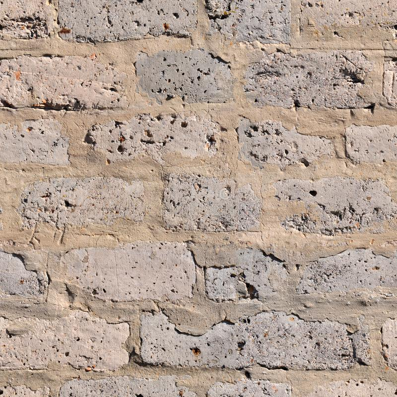 Repeating seamless background of an old wall folded from gray cinder block. Repeating seamless pattern of an old, weathered wall with wide cement seams royalty free stock photos