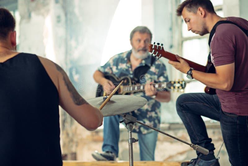 Repetição da faixa da música rock Guitarrista e baterista bondes atrás do grupo do cilindro fotografia de stock royalty free