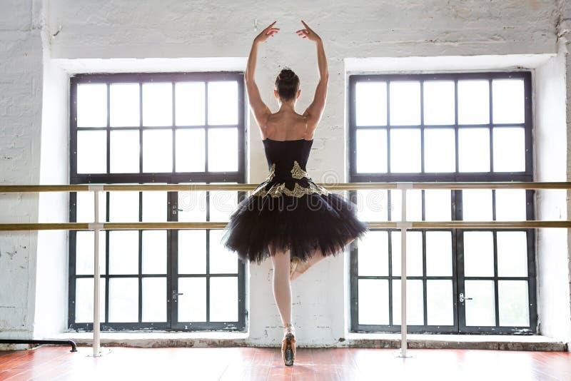 Repetitieballerina in de zaal Houten vloer, zeer grote vensters Mooie ballerina in de repetitieruimte stock foto's
