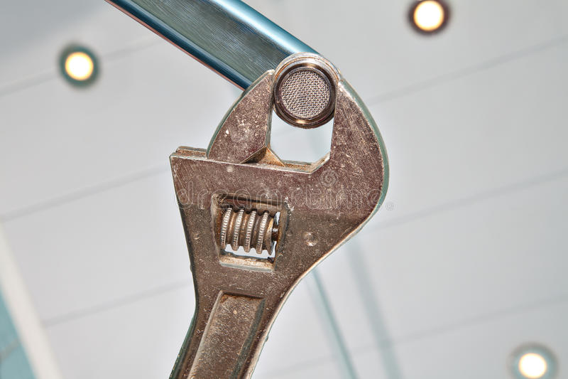 Replace Sink Aerator, using adjustable plumbing spanner, hands p. Fixing a Faucet Aerator, using an adjustable wrench plumber, hands handyman close-up royalty free stock images