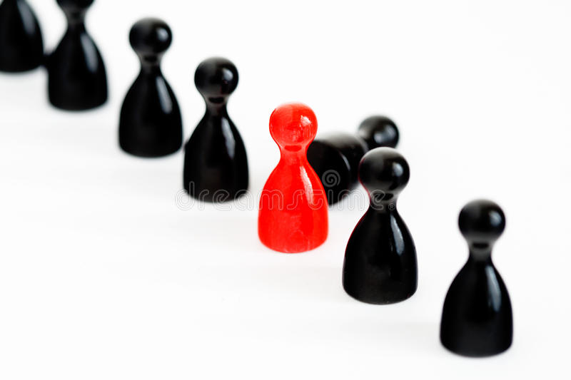Replacement. A row of black game figurines with a red one symbolizing the replacement of one stock photos