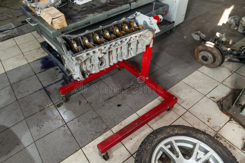 Replacement engine used on a crane mounted for installation on a car after a breakdown and repair in a car repair workshop as a stock photos