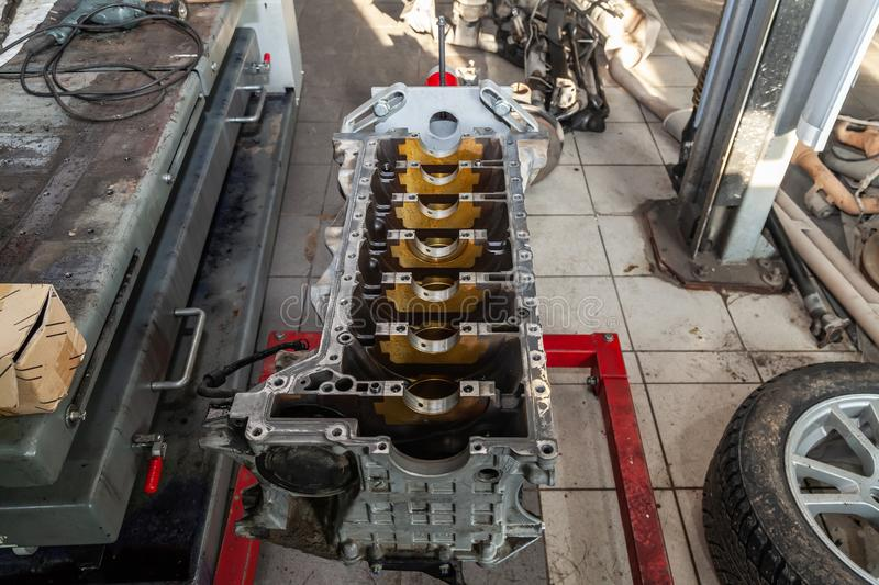 Replacement engine used on a crane mounted for installation on a car after a breakdown and repair in a car repair workshop as a stock image