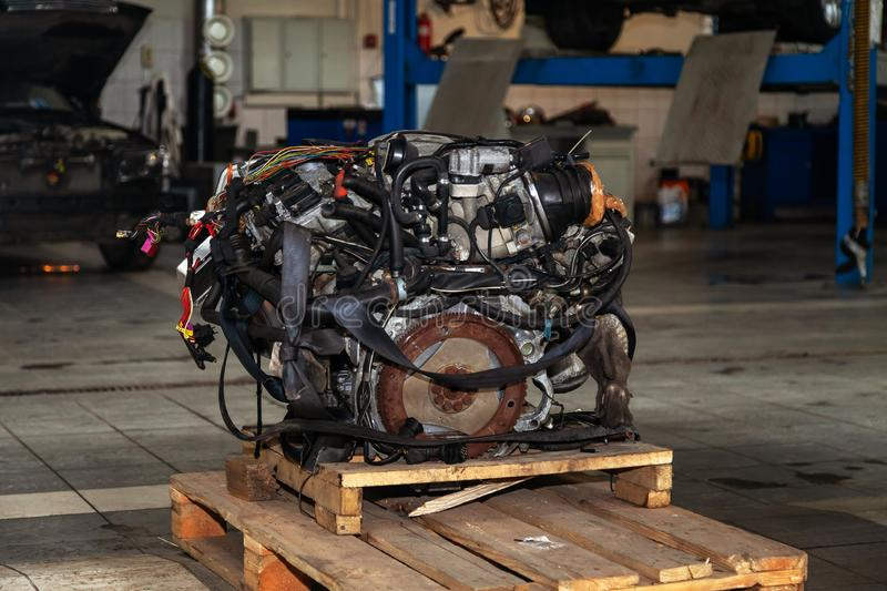 Replacement engine used on a pallet mounted for installation on a car after a breakdown and repair in a car repair workshop as a royalty free stock images