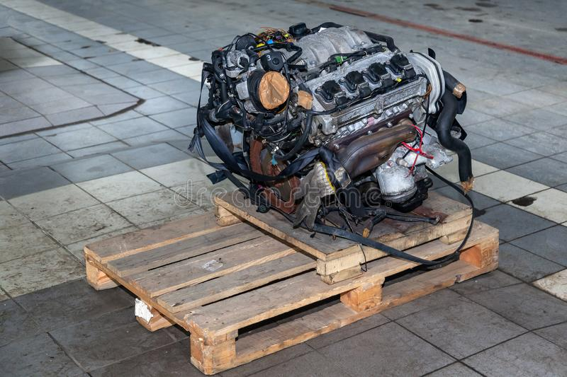 Replacement engine used on a pallet mounted for installation on a car after a breakdown and repair in a car repair workshop as a stock photography