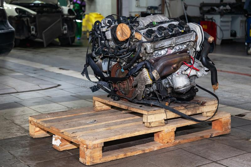 Replacement engine used on a pallet mounted for installation on a car after a breakdown and repair in a car repair workshop as a royalty free stock image
