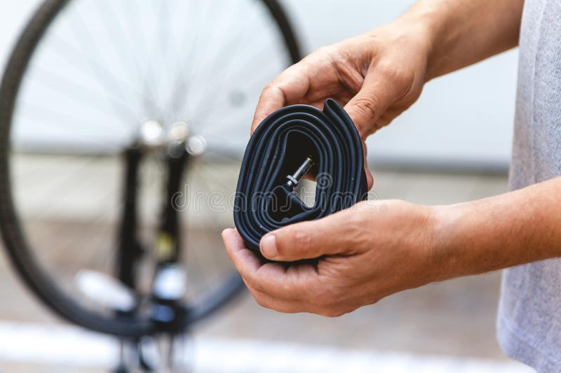 Cyclist hands are holding collapsed rubber bicycle camera stock images