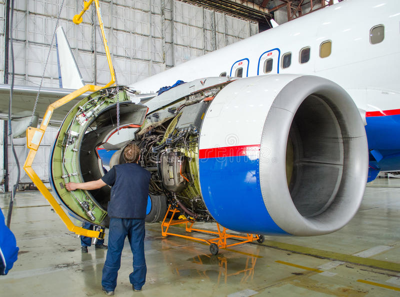 Replacing the engine on the plane, working people tap. Concept maintenance of aircraft. stock images