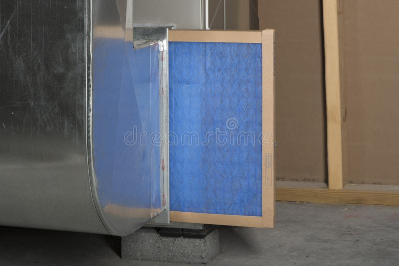 Replacing Furnace Filter. A furnace filter in the process of being replaced stock photo
