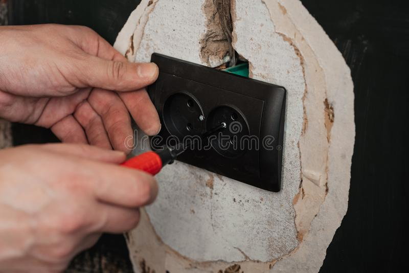 Replacing and installing a new electrical outlet. Hands with a screwdriver male electrician royalty free stock image