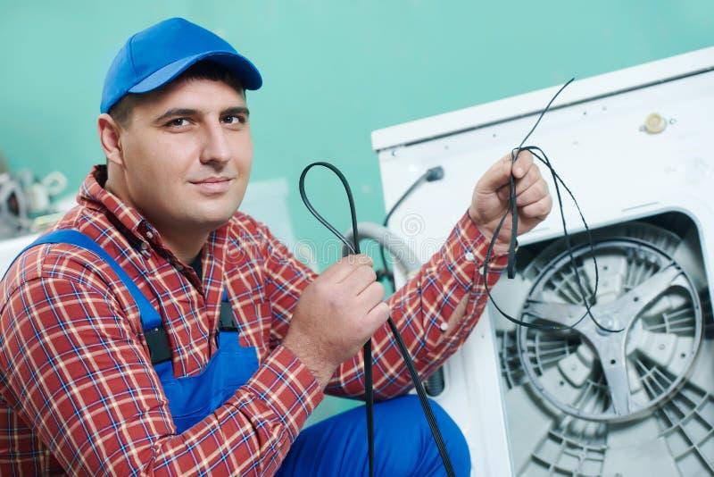 Replacing rubber drive belt of washing machine royalty free stock photo