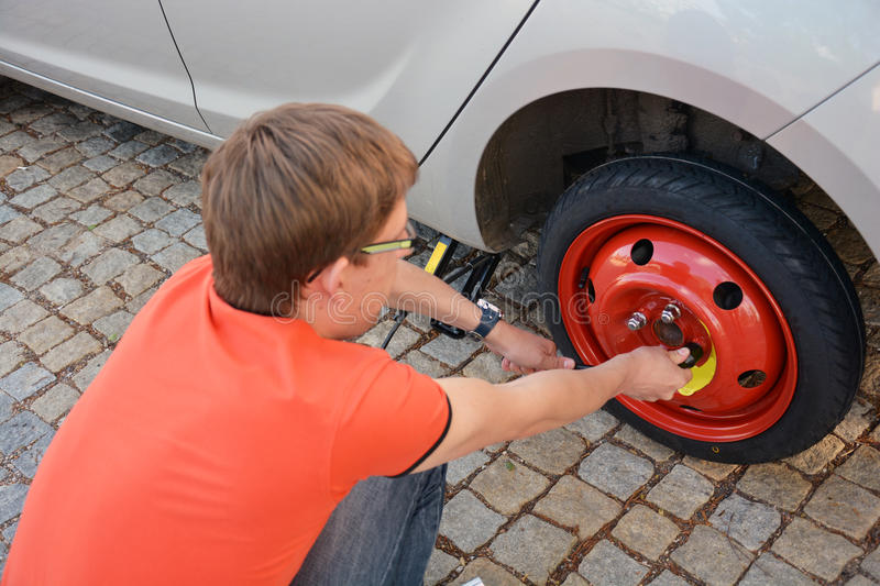Replacing the tires on the car. Flat tire. Attaching a spare wheel. Lifting the car on the jack. Accident with punctured tires. Hard man work stock images