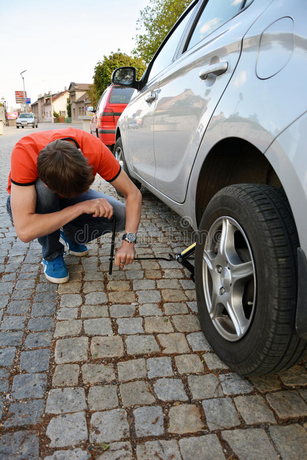 Replacing the tires on the car. Flat tire. Attaching a spare wheel. Lifting the car on the jack. Accident with punctured tires. Hard man work royalty free stock photo