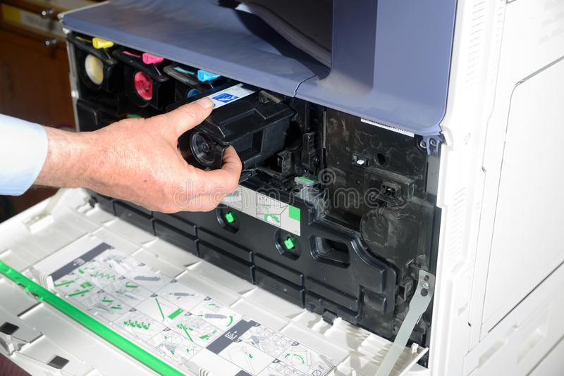 Replacing toner. An office worker replaces a black toner cartridge in a photocopier royalty free stock image