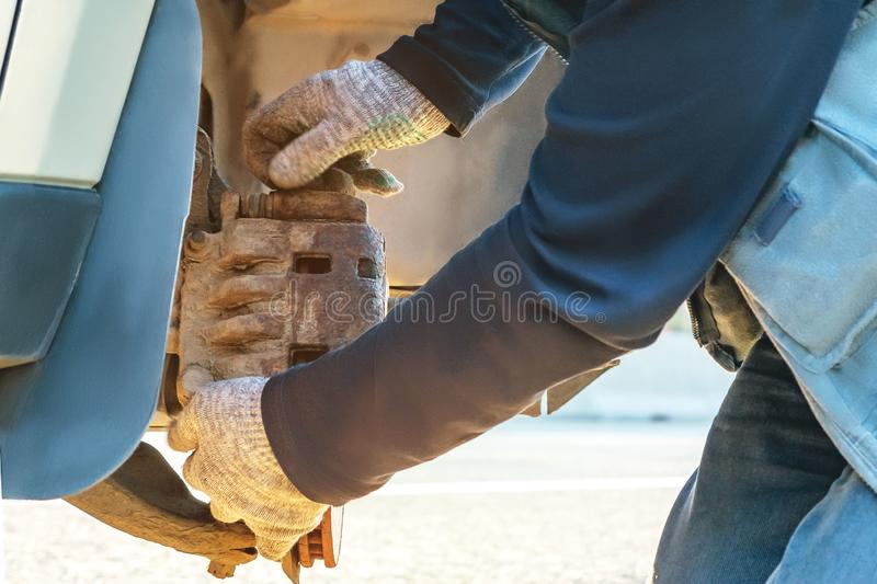 Replacing the wheel on the highway, the car is jacked, inspection and removal of brake pads stock photo