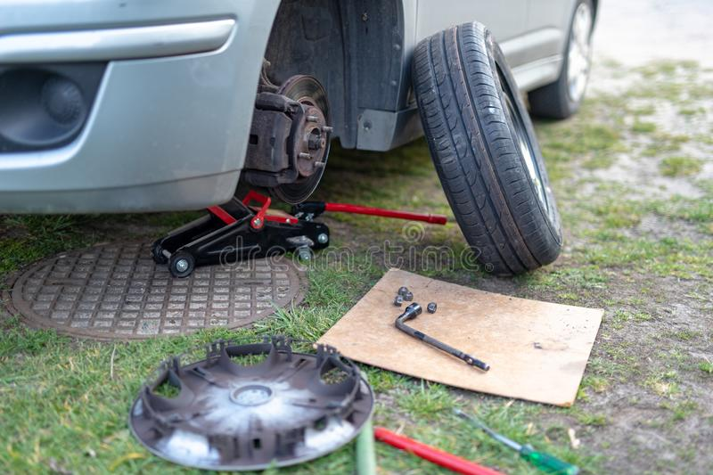 Replacing the wheel in a passenger car. Changing wheels from winter to summer. Season of the spring stock photo
