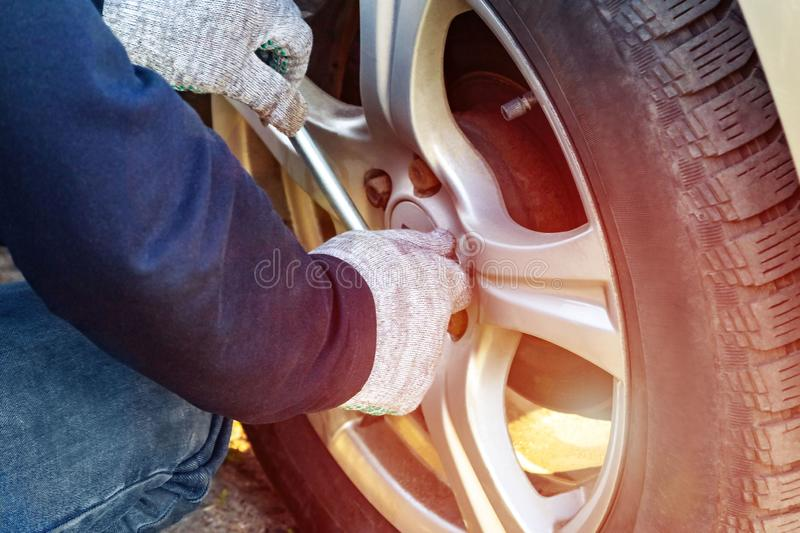 Replacing the wheels on the highway, the car is jacked, the men`s hands Unscrew the nuts with a tire iron royalty free stock photography