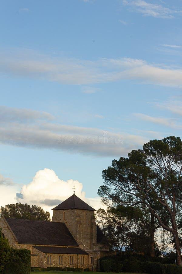 Replica di vecchia chiesa del mattone sulla sommità con il euvalyptus e sui pini con la vista panoramica della nuvola fotografia stock libera da diritti