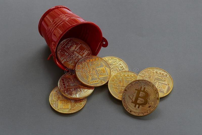 Replica of golden bitcoin fall from red pile.Grey background. Business and finance concept. stock image