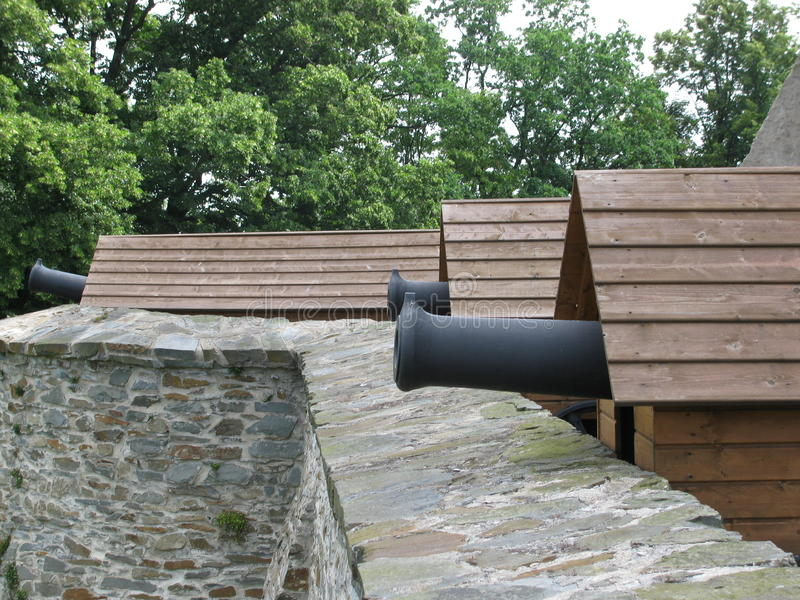 Replica of historic cannons at the castle. Replica of historics cannons at the castle bouzov placed on the gallery walls, in the background trees around a wall royalty free stock photos