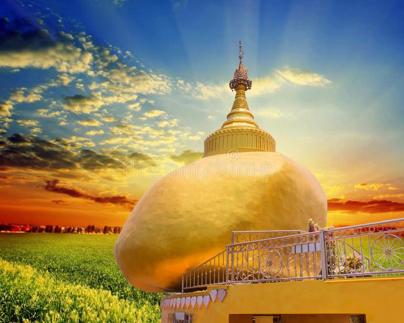 The replica of Phra That In-Kwaen Hanging Golden Rock with Sunset background, Sirey temple, Phuket, Thailand. stock photos