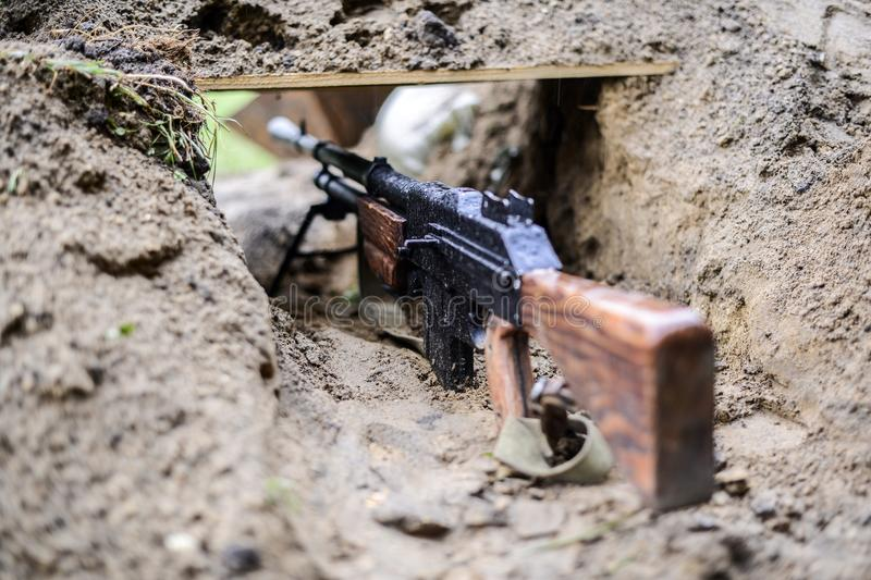 A replica of a rifle from World War II in the trench. stock image
