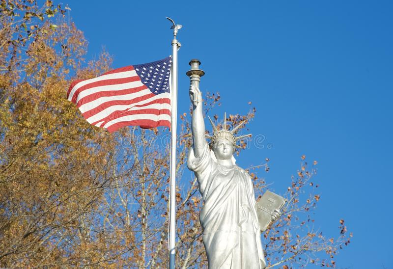 Statue of Liberty Replica. Replica of the Statue of Liberty with the Flag of the United States flying nearby stock photos