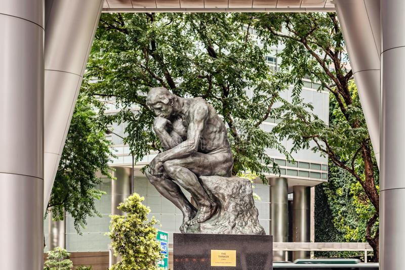 Replica of The thinker sculpture bu Auguste Rodin in Singapore city. Singapore - Jan 14, 2018: Replica of The thinker sculpture bu Auguste Rodin at OUE Tower in stock photography