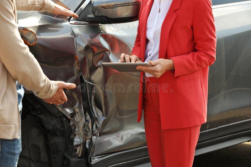Reportage d'homme et agent d'assurance avec le formulaire de réclamation remplissant de comprimé près de la voiture cassée photos stock