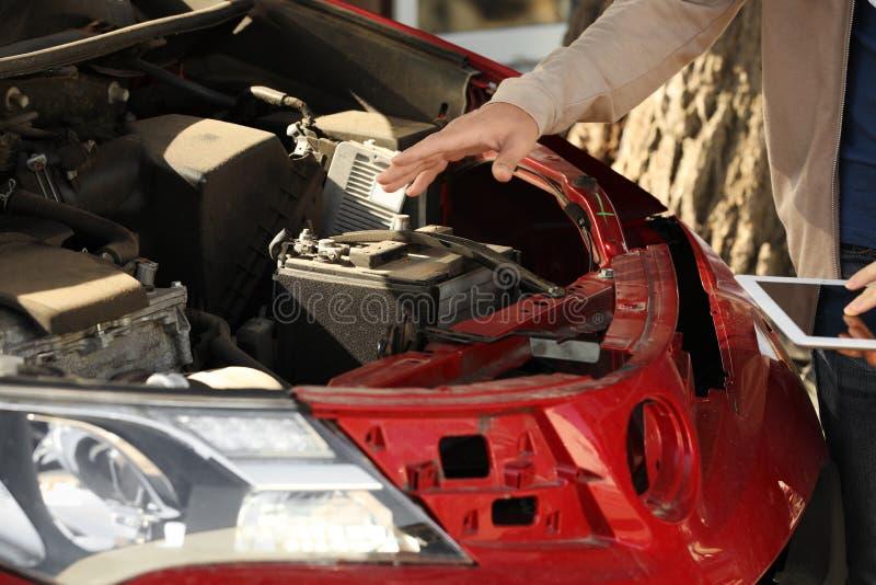 Reportage d'homme et agent d'assurance avec le formulaire de réclamation remplissant de comprimé près de la voiture cassée images libres de droits