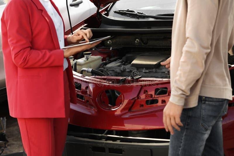 Reportage d'homme et agent d'assurance avec le formulaire de réclamation remplissant de comprimé près de la voiture cassée photo libre de droits