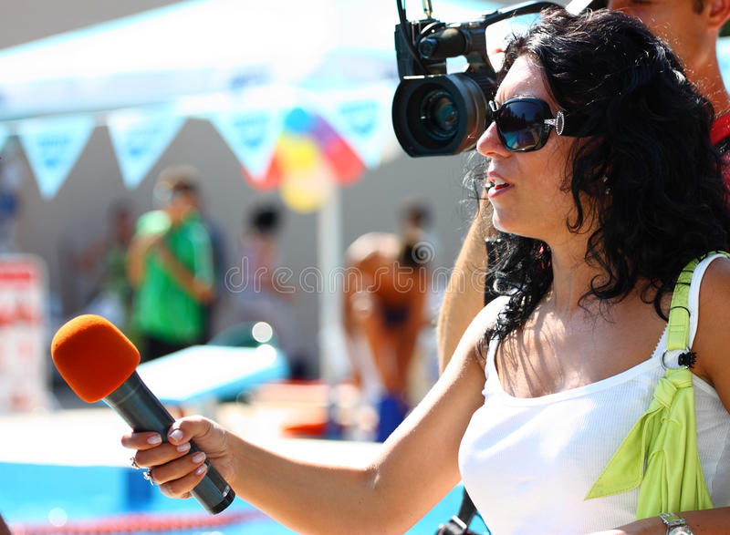Reporter. A television news reporter in live transmission taking interview stock photos