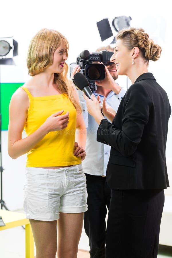 Reporter and cameraman shoot an interview stock photos