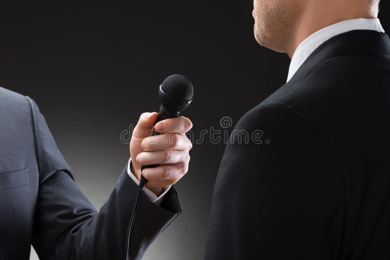 Reporter conducting interview of businessman. Close-up Of A Reporter Conducting Interview Of Businessman royalty free stock photos