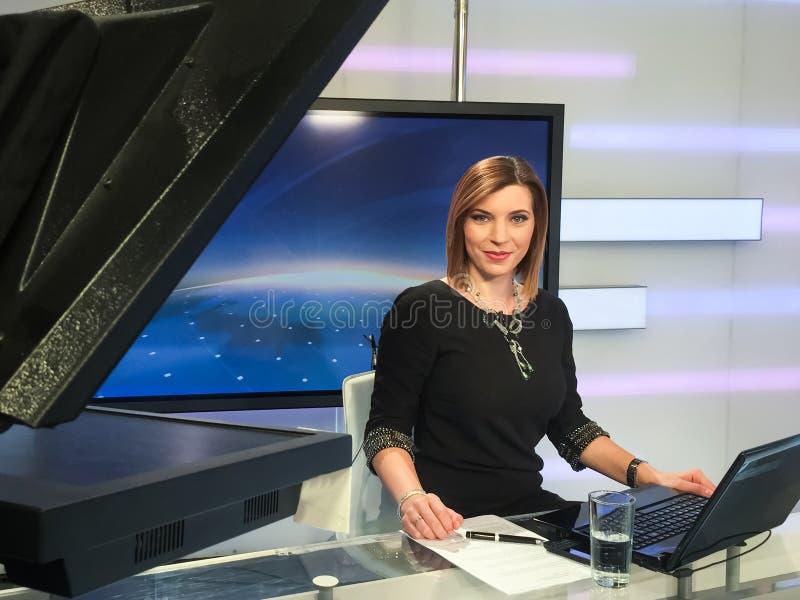 Reporter della TV allo scrittorio di notizie immagine stock libera da diritti