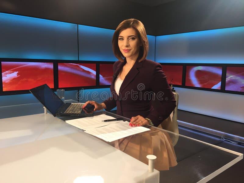 Reporter della TV allo scrittorio di notizie immagine stock