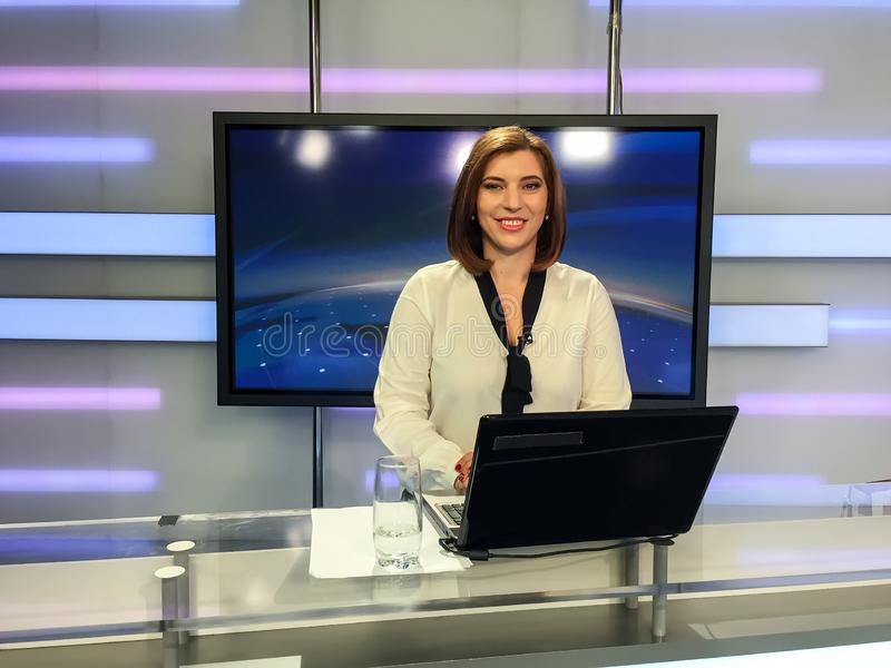 Reporter della TV allo scrittorio di notizie fotografie stock
