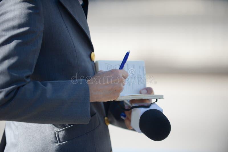 Reporter, der seine Anmerkungen in ein Notizbuch schreibt und das Mikrofon hält lizenzfreie stockfotos
