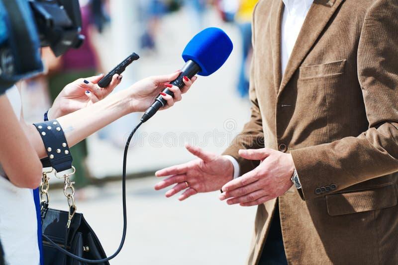 Reporter di media con il microfono che fa intervista del giornalista per le notizie fotografie stock
