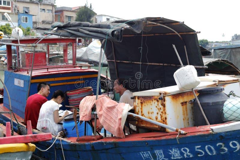 Reporter intervjuade den gamla fiskaren på shapoweien beskyddade skeppsdockan, den amoy staden, porslin royaltyfri foto
